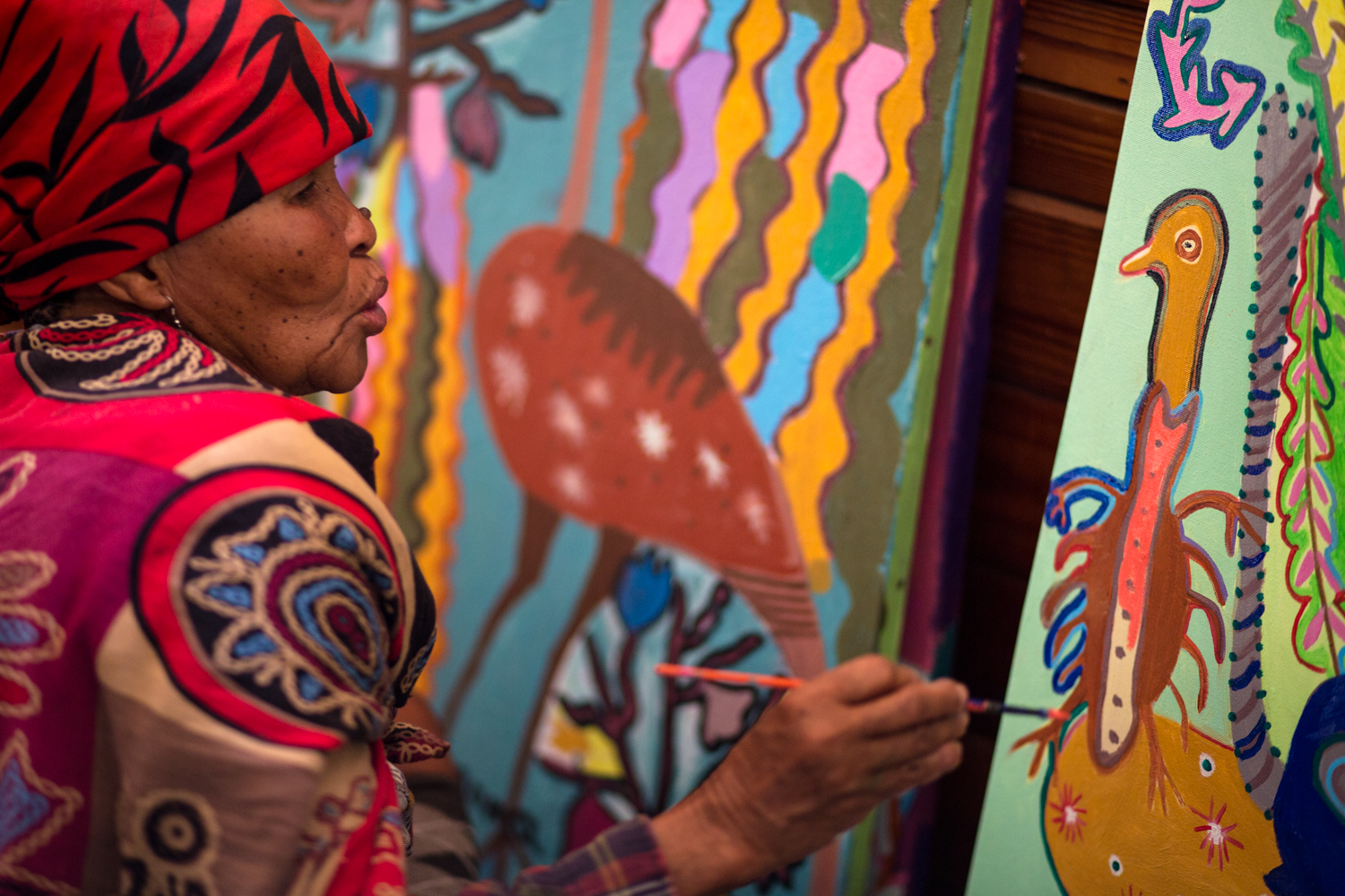 Cgoma Simon, a San woman and artist at the Kuru Art Project in D'kar, Botswana, works on a painting in the art studio on June 21, 2017.