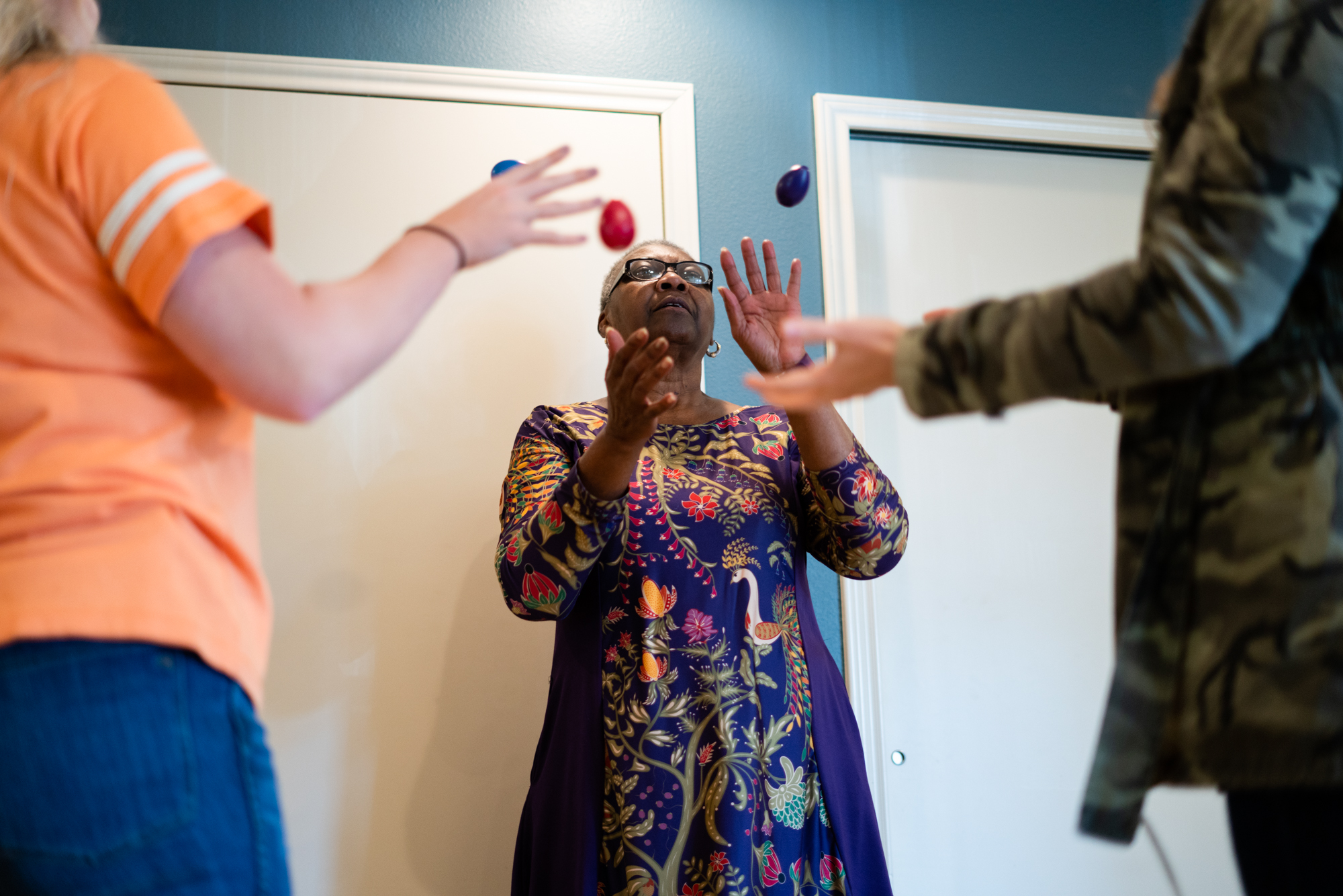 Davis practices an egg toss exercise with two therapists. Hand-eye coordination exercises are routine in her therapy sessions.