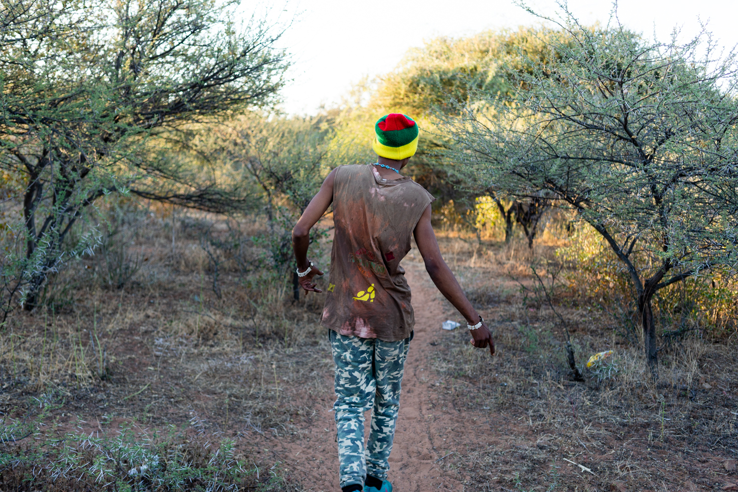Alphynho walks along a dirt path back to his house. He always has music playing on his phone in his pocket and sings a dances wherever he goes.