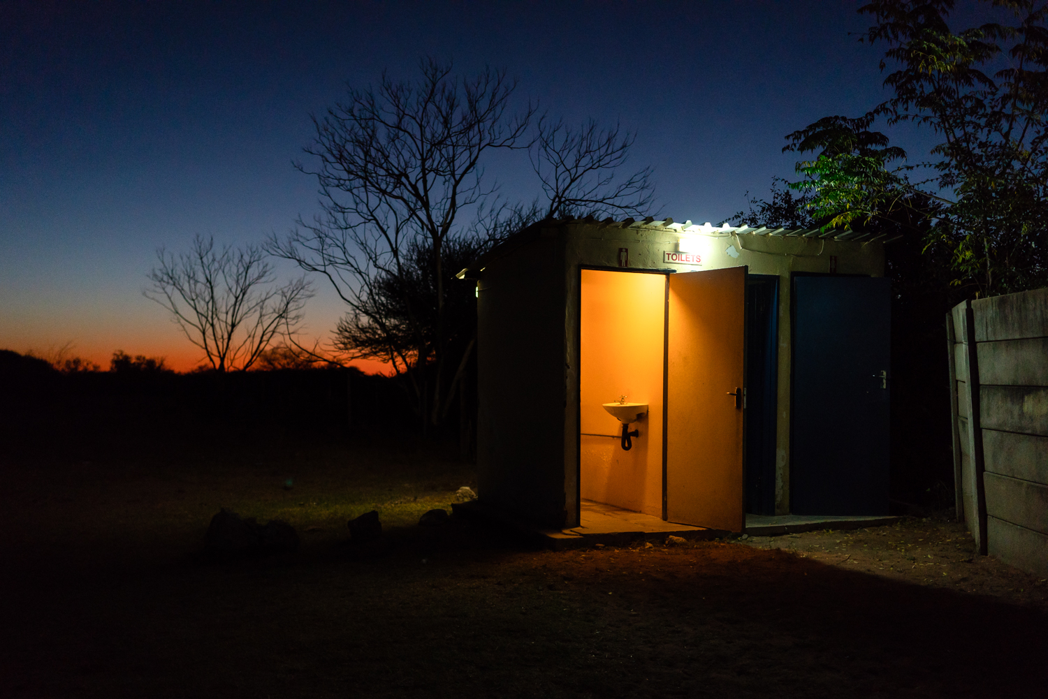Toilets outside of the only bar in D'kar as the sun sets.