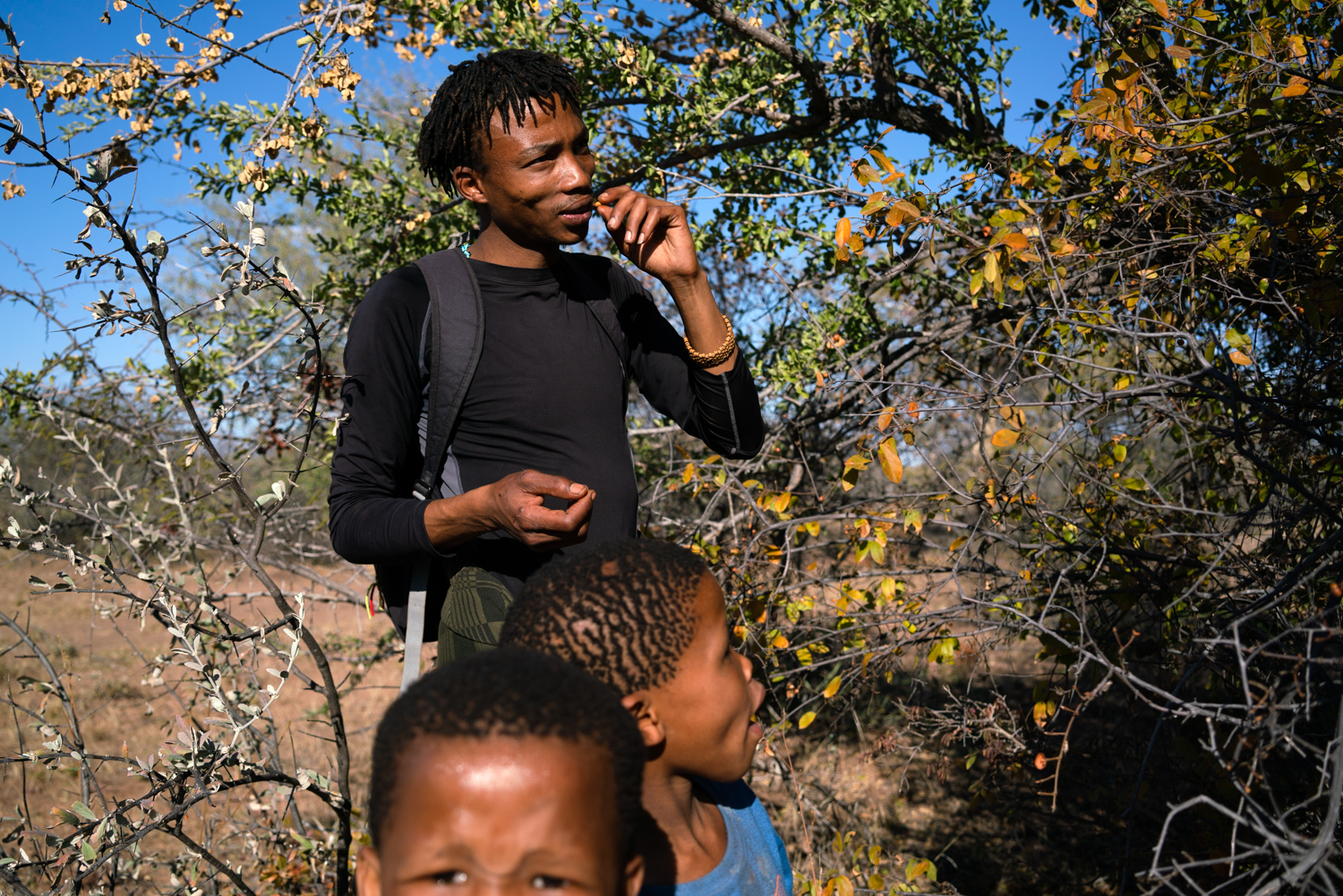 Alphynho eats some berries while on a bush walk with his girlfriend and her nieces and nephews. Gathering berries is a tradition for the San, but many young people reject this practice.