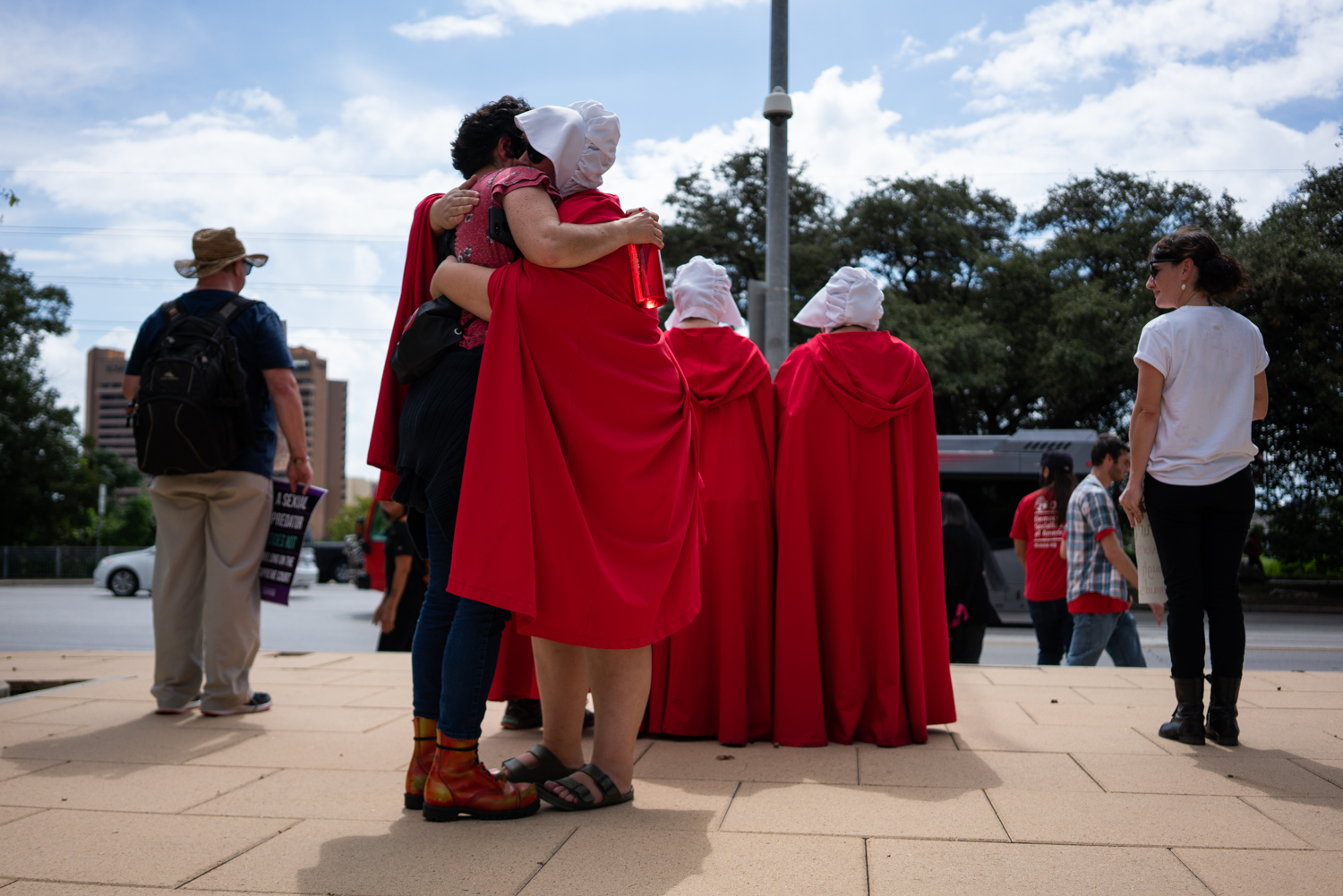 A passerby hugs a member of the Texas Handmaids after a march from the Texas State Capitol to Austin City Hall protesting the confirmation of Brett Kavanaugh to the U.S. Supreme Court. Oct. 6, 2018.