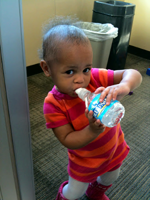 A Scholar's child takes a water break during a training.