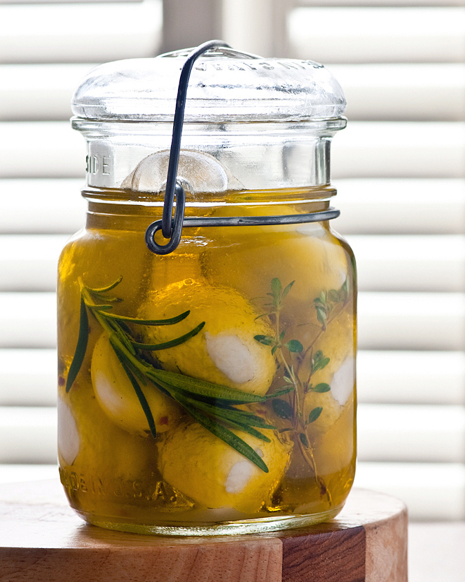 Homemade Bocconcini marinating in olive oil and fresh herbs.