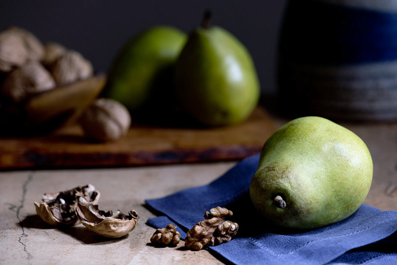 In this example, I stood to the right of my shooting table and moved the flashlight up and down, starting in the foreground and working my way toward the back.  I spent about 20 seconds with my light on the foreground, and about 10 seconds on the background, so the foreground pear and walnut are brighter than those in the background.