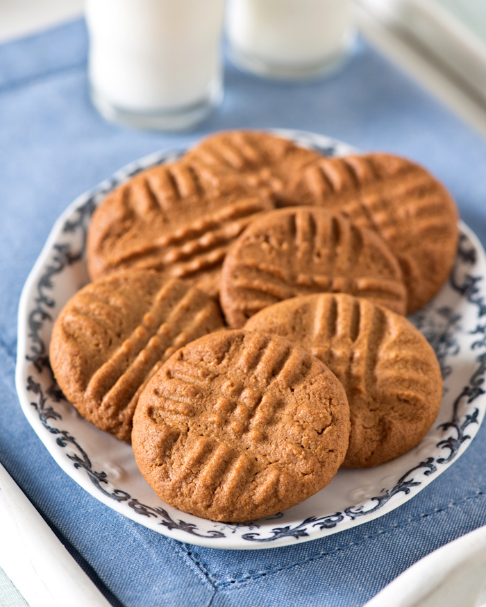 Easiest Peanut Butter Cookie recipe ever is a childhood treat served on a vintage china plate with cold glasses of milk, evoking fond memories of grandma's house.