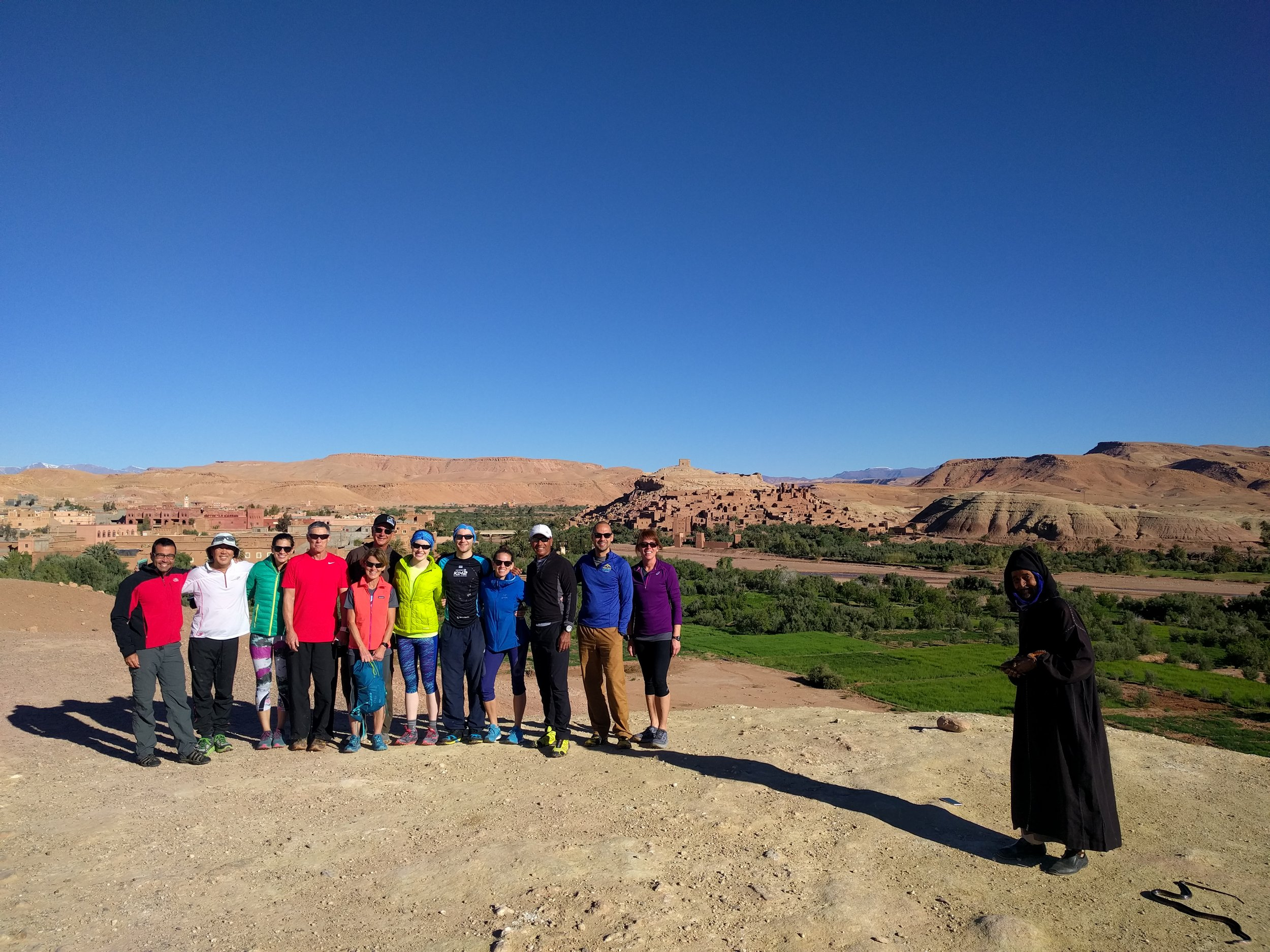 Our Endurance Adventure group in front of Ait Ben Haddou and lush green fields. Local snake charmer approves.