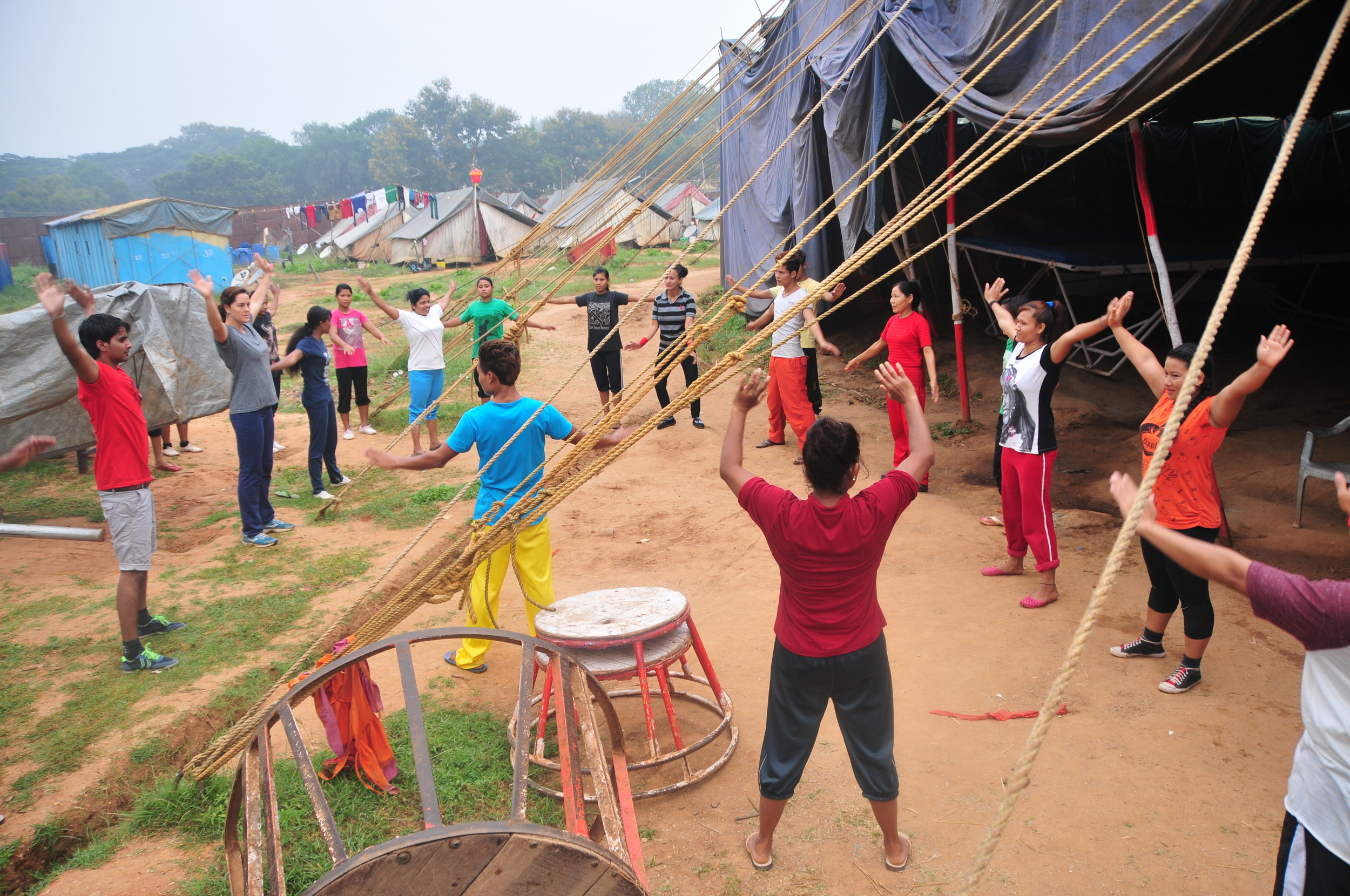 Early morning warm up to prepare for daily training at backstage of the big top, home tents in the background. Photo: John Nyagah