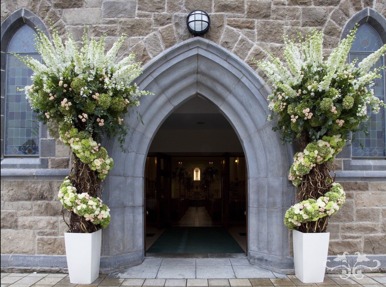 Two tall arrangements offer an alternative to the traditional floral arch. Delphinium, Agapanthus, green Hydrangea, peach Spray Rose, Avalanche Rose, Carnation and Eucalyptus on a pillar construction of Contorted Hazel.