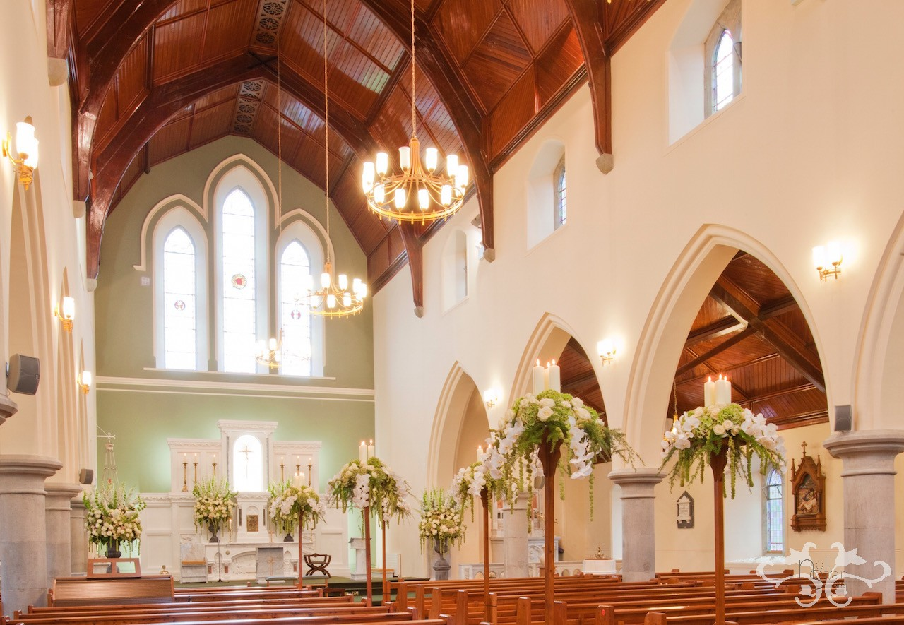 Gothic arches inspired lavish floral decorations with church candles floating high above the pew ends to line the aisle.