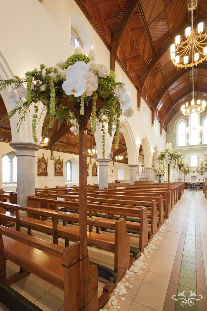 Magnificent pew end arrangements with lighted candles bring your eye up the aisle to the altar.