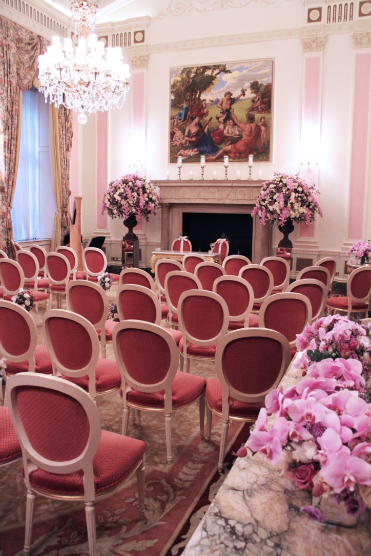 The pink Phalaenopsis Orchids capture the pale pink of the wall columns and the coral pink of the chairs.