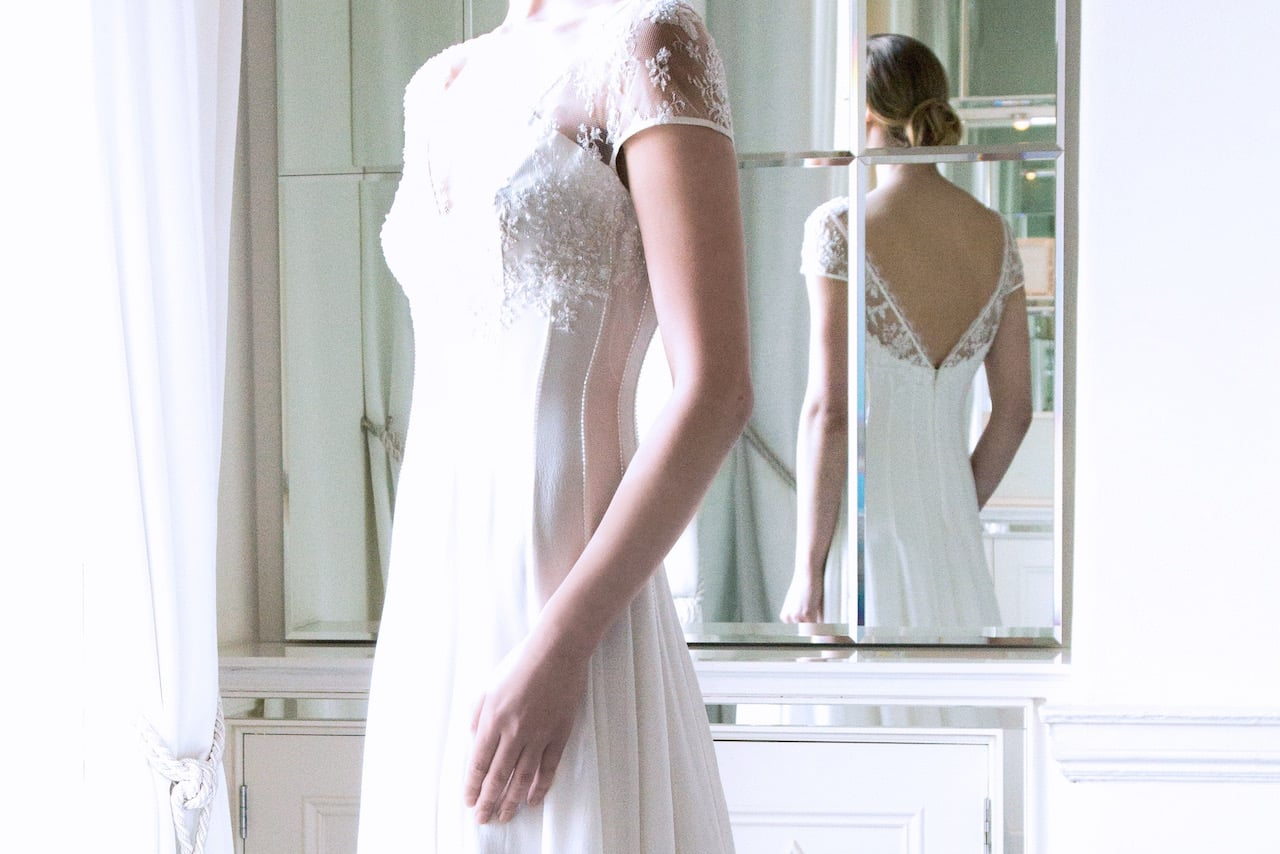The 'Zarah' Ivory Silk Lace Bridal Gown with Swarovski Encrusted V-Neckline €5995 dictates to me delicate spray Roses in different shades of ivory, apricot or very pale pink.