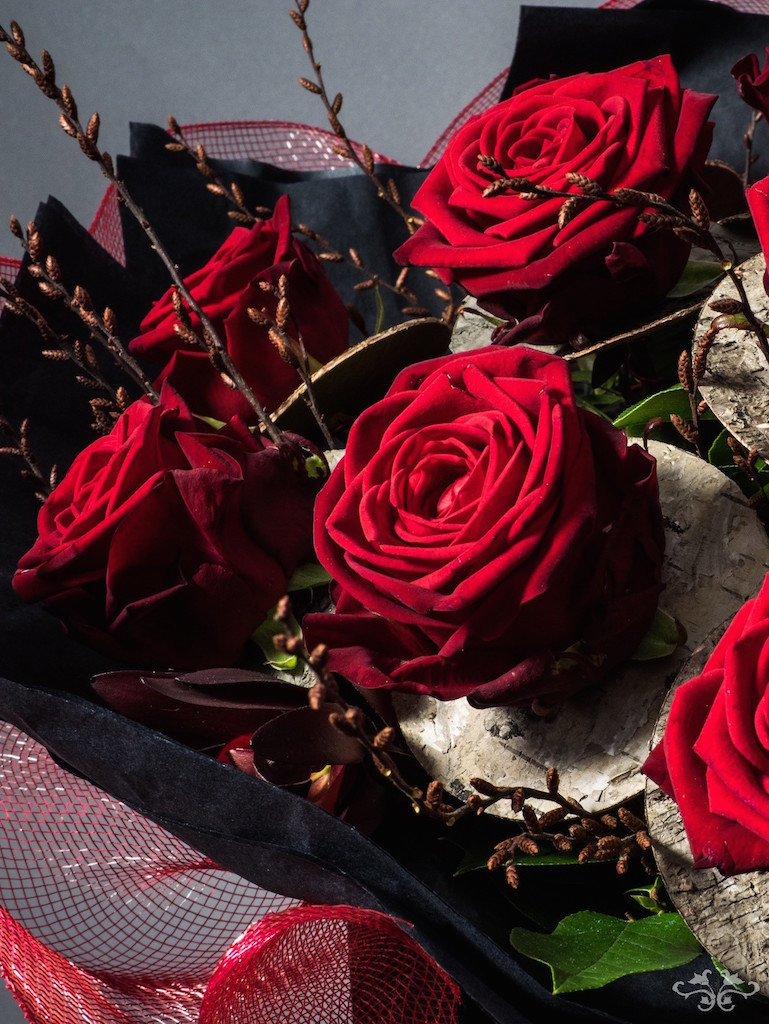 Birch bark and twigs add a contemporary look to the magnificent Red Naomi Roses.