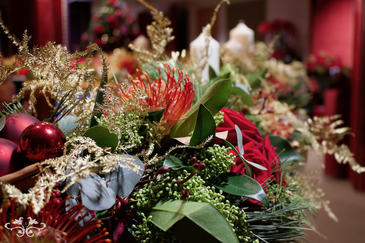 Fresh Roses, Protea, berries and gold sprayed fern enrich the seasonal foliage and baubles in a garland.