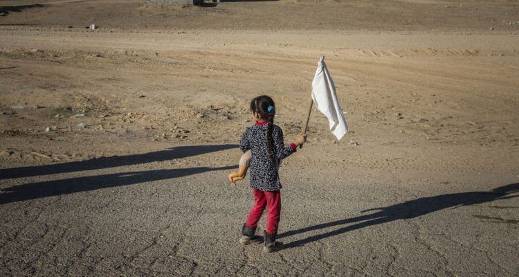 A young girl carrying a teddy bear and waving a white flag, heads towards an army outpost in the Samah neighbourhood on the eastern outskirts of Mosul, away from the heavy fighting engulfing the city. Photo: UNHCR/Ivor Prickett