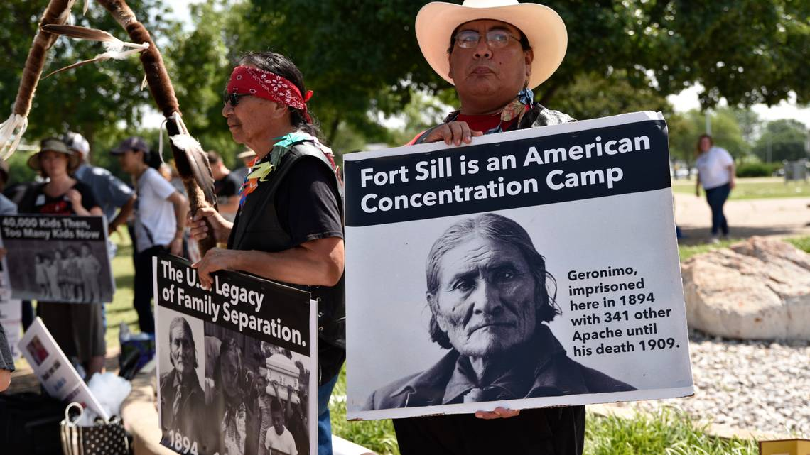 Toma Hubert, left, a Lakota Sioux tribe member, and Michael Topaum, with the Kiowa Tribe of Oklahoma, protest plans to house migrant children at Fort Sill, in Lawton, Okla., June 22, 2019. Protesters called the plan for the site, home to an internment camp for Japanese Americans during World War II, a return to one of the nation's great shames. NICK OXFORD NYT