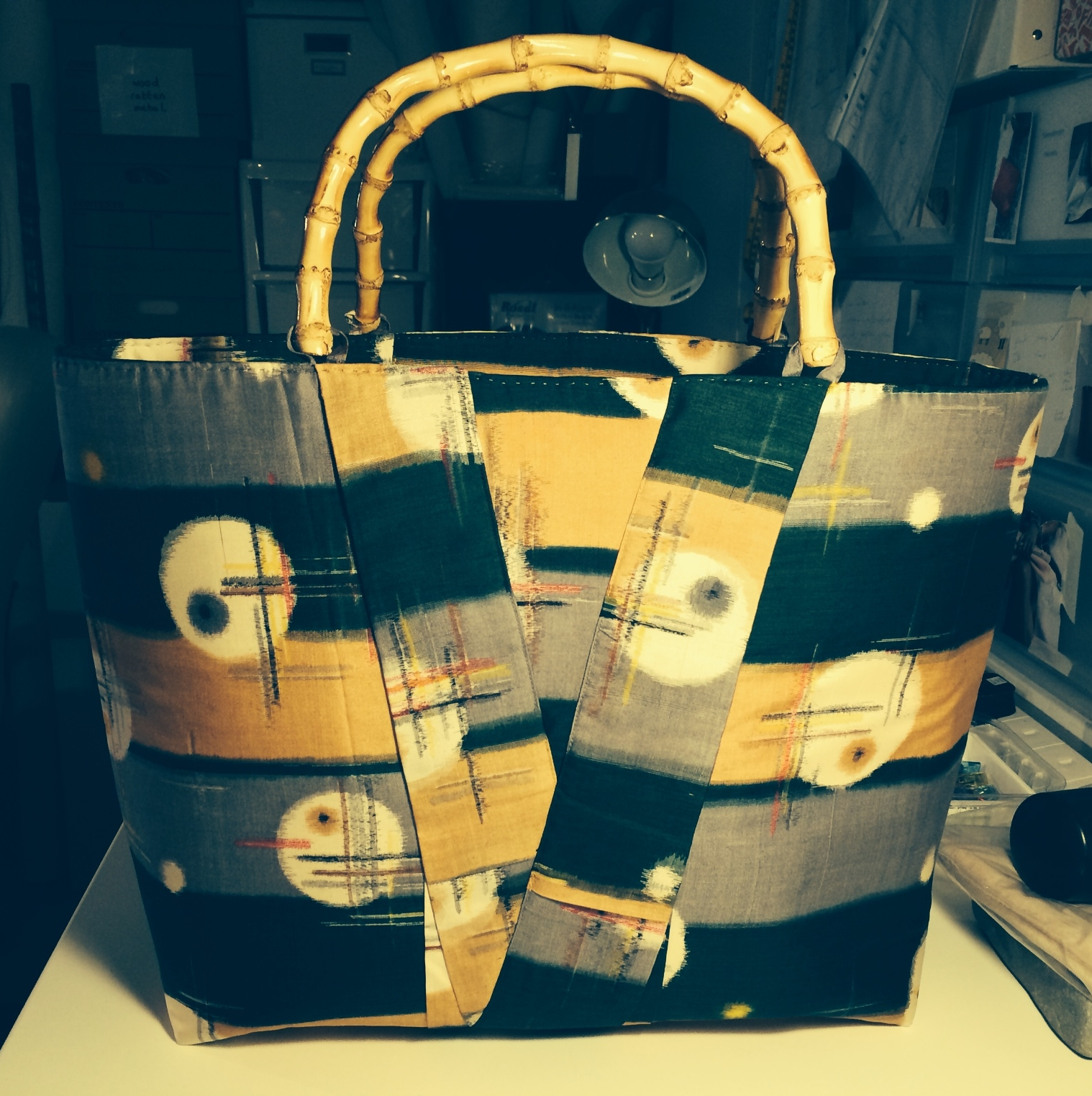 A workshop phone snap. A vintage Japanese silk kimono was reworked to create a large tote bag with bamboo handles and wooden ball feet.