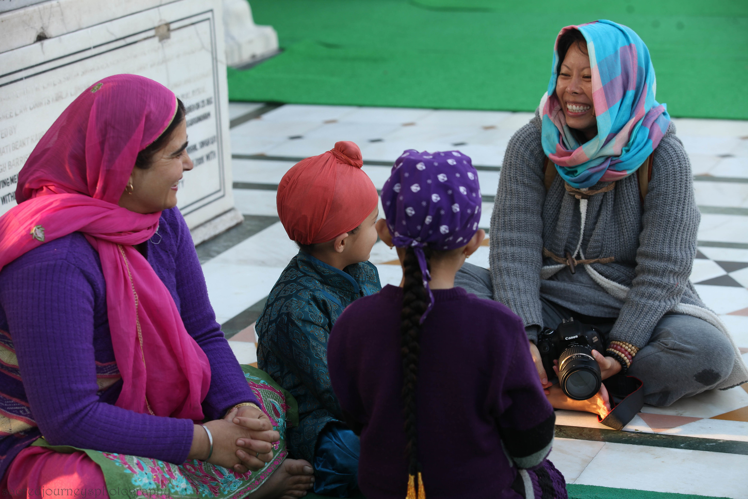 Rita from Hong Kong, having a great time with a family on the Parkarma of the Golden Temple in Amritsar India ~ Sacred Journeys  INDIA encourages positive cultural exchanges