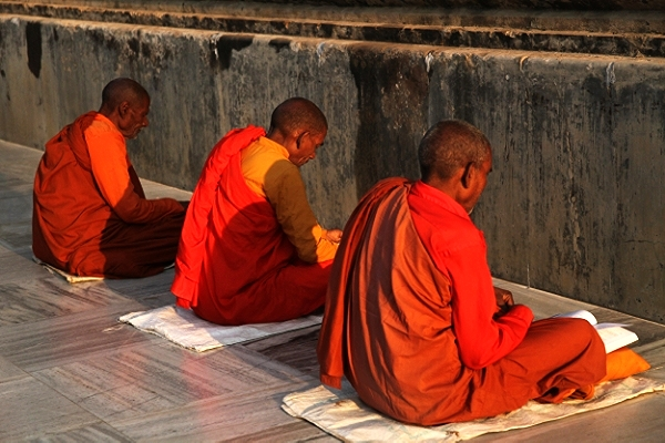 Monks in morning devotional practice facing the base of the Maha Bodhi Temple ~ Bodhgaya