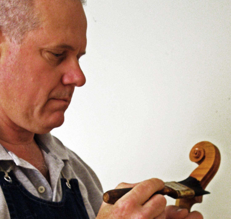 Jim McKean varnishing a violin scroll