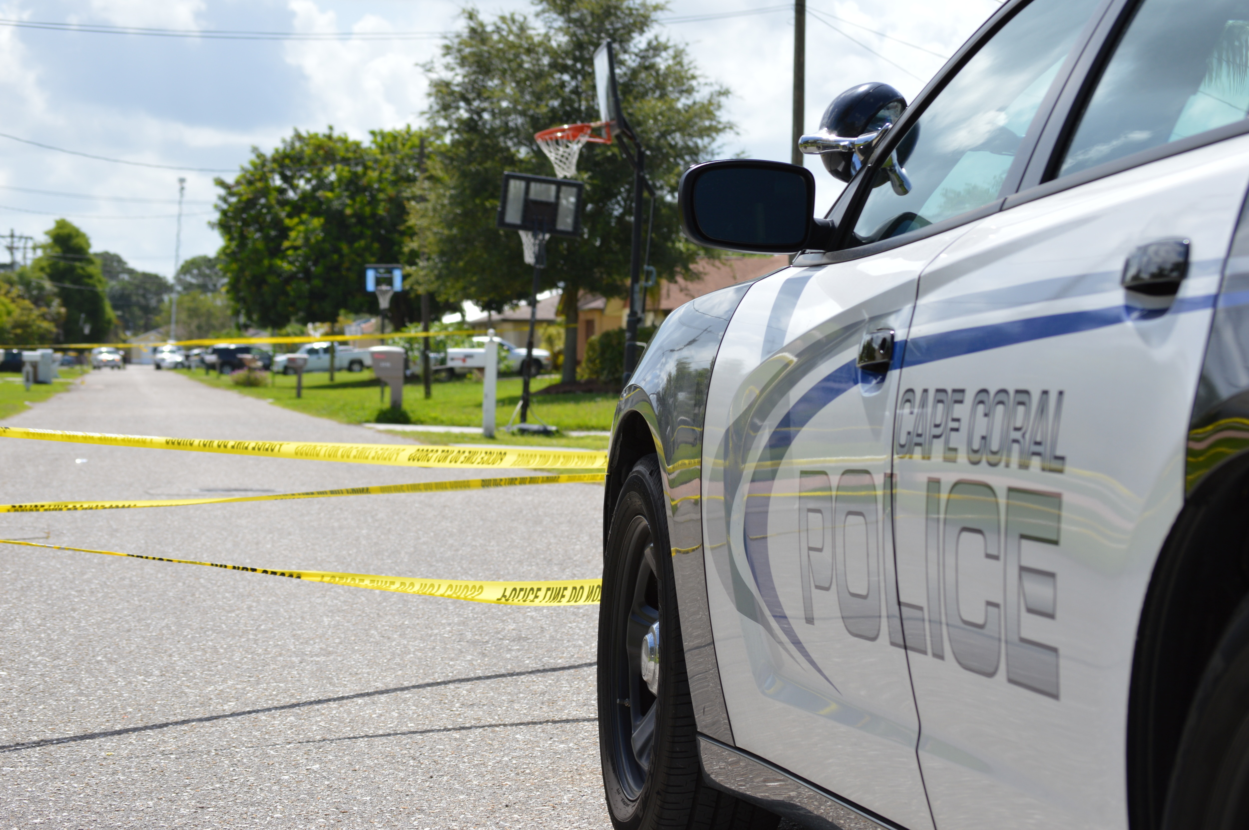 PHOTO: A Cape Coral Police Department patrol car guards an entry point to a taped-off crime scene in a residential neighborhood. Yellow crime scene tape blows in the breeze in front of the marked cruiser. (Photo Courtesy of Cape Coral Police Department)