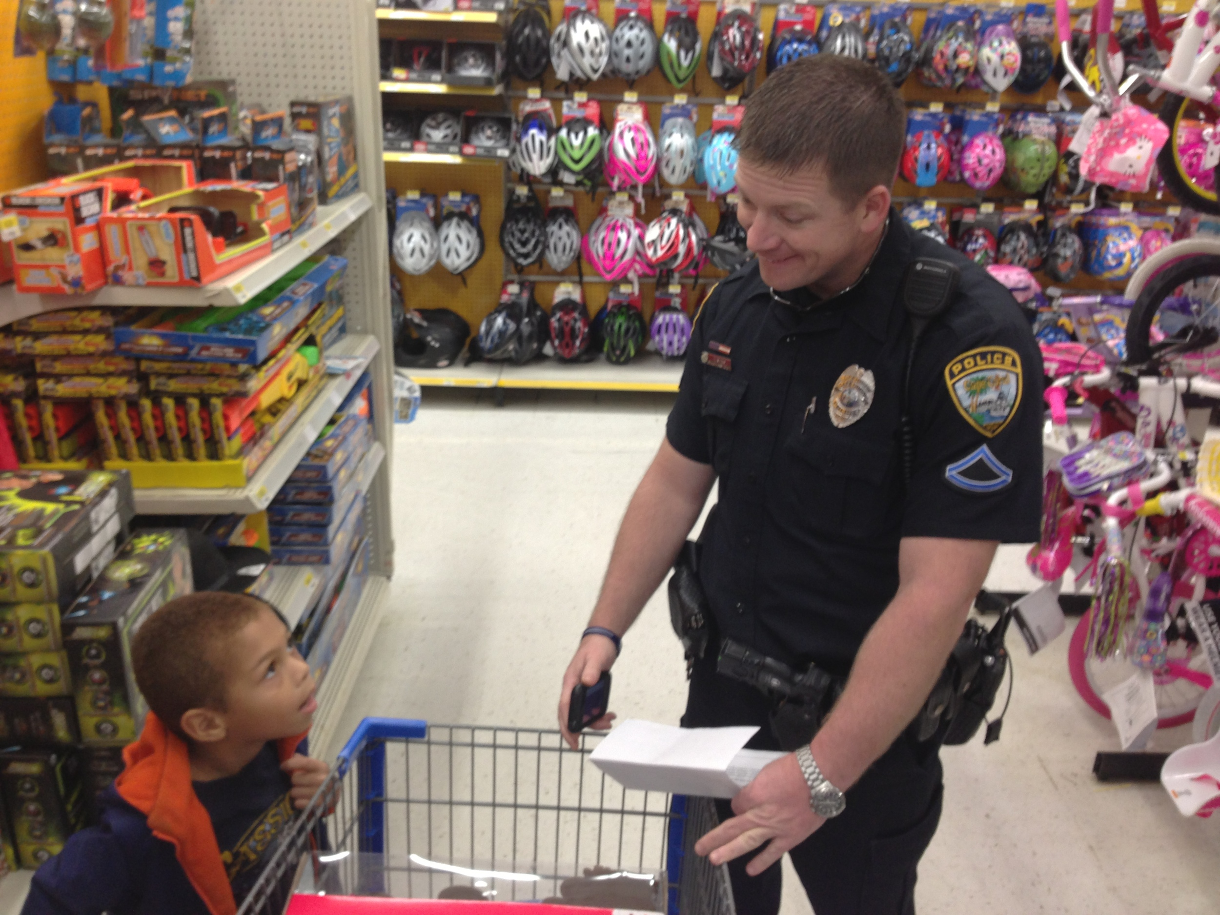 """PHOTO: Officer John Kuhn goes over the shopping list with his """"partner"""" at the 2012 Shop With A Cop. (Photo Courtesy of Cape Coral Police Department)"""