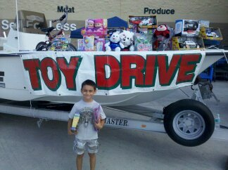"""PHOTO: An image to the boat from last year's """"Fill the Boat"""" Toy Drive. Posing in front is a young donor. (Photo Courtesy of Cape Coral Police Department)"""