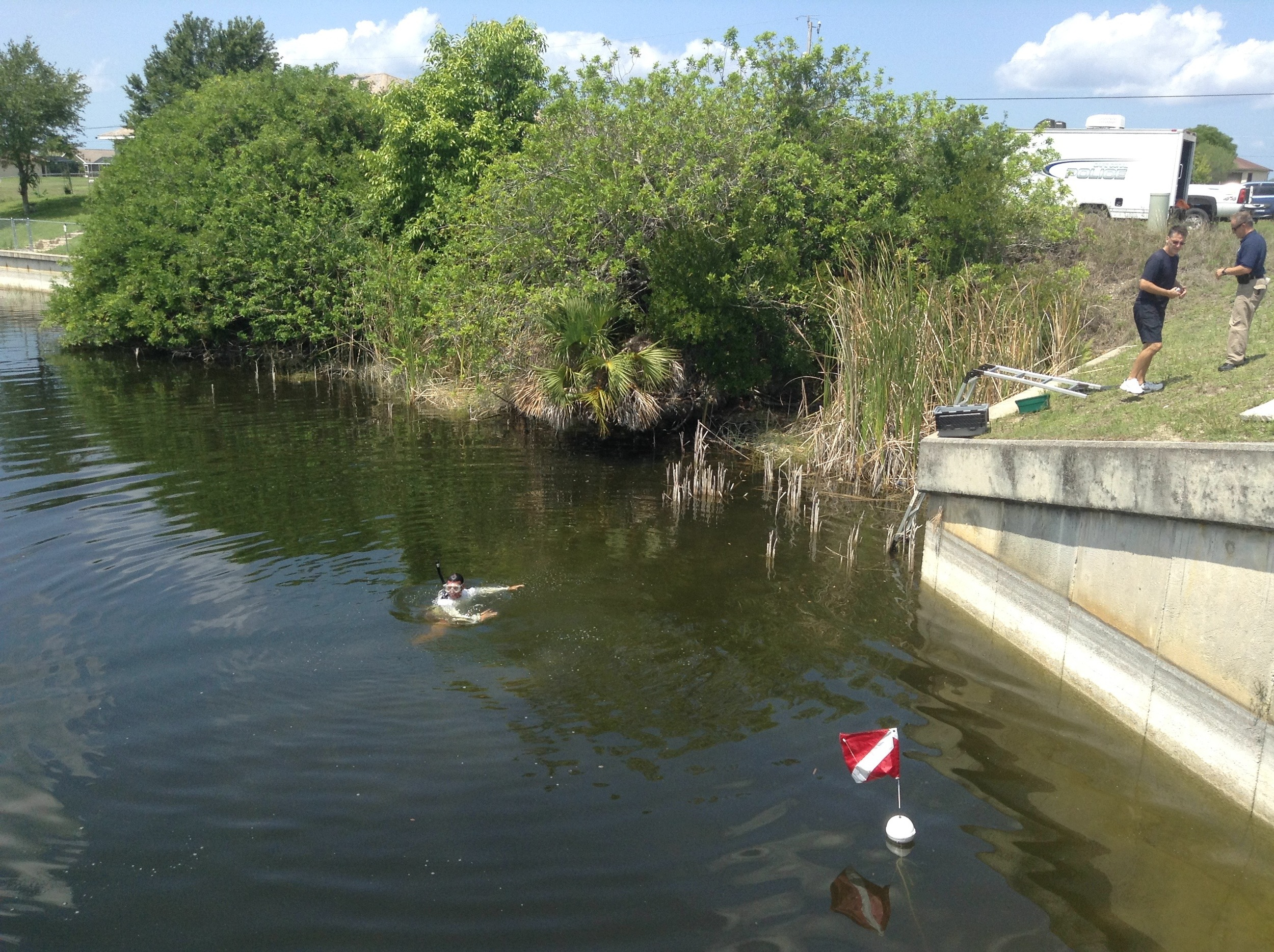 PHOTO: Officer Christian Munoz-Luna surveys an area in a canal where electronics were just located. (Photo Courtesy of Cape Coral Police Department)