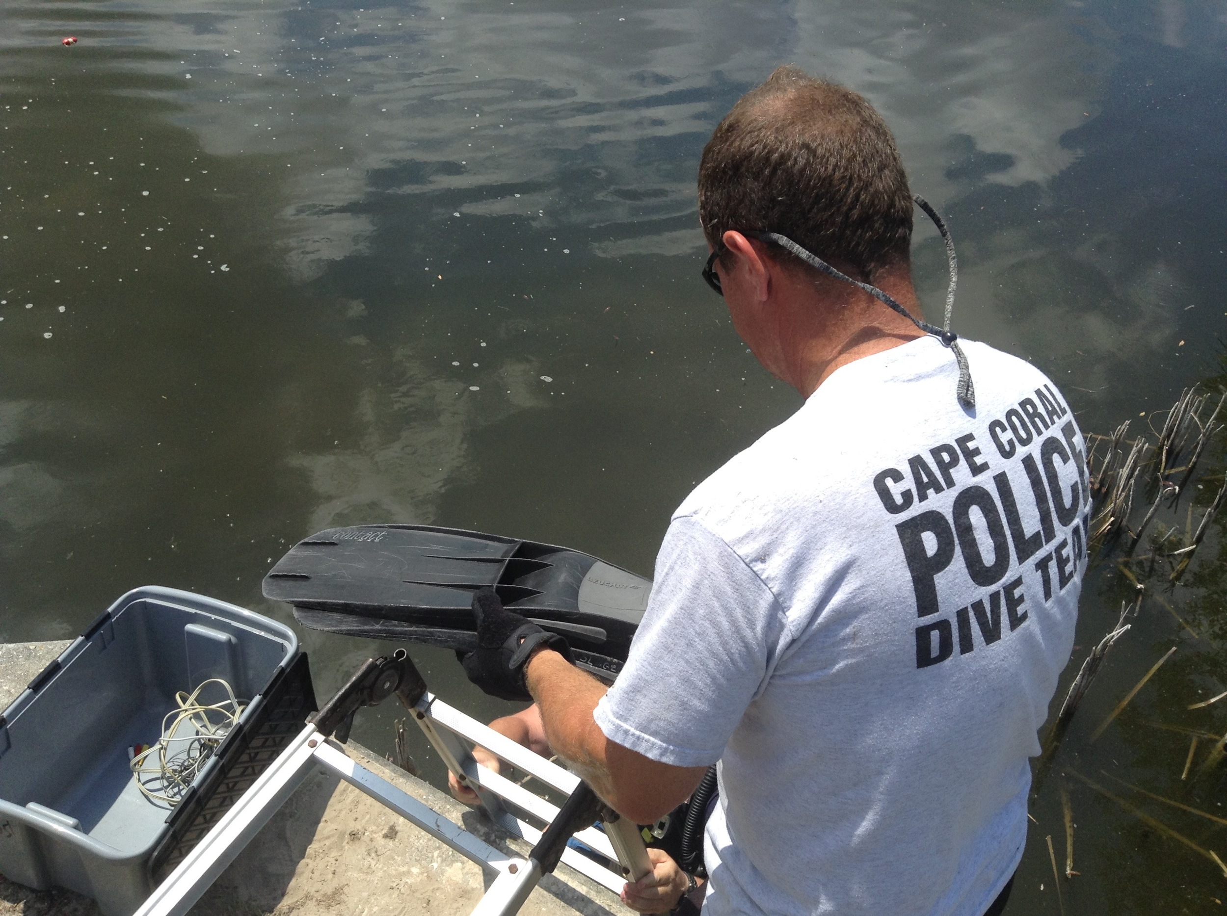 PHOTO: Cpl. Howard Post assists another diver into the water and is about to hand him his flippers. (Photo Courtesy of Cape Coral Police Department)