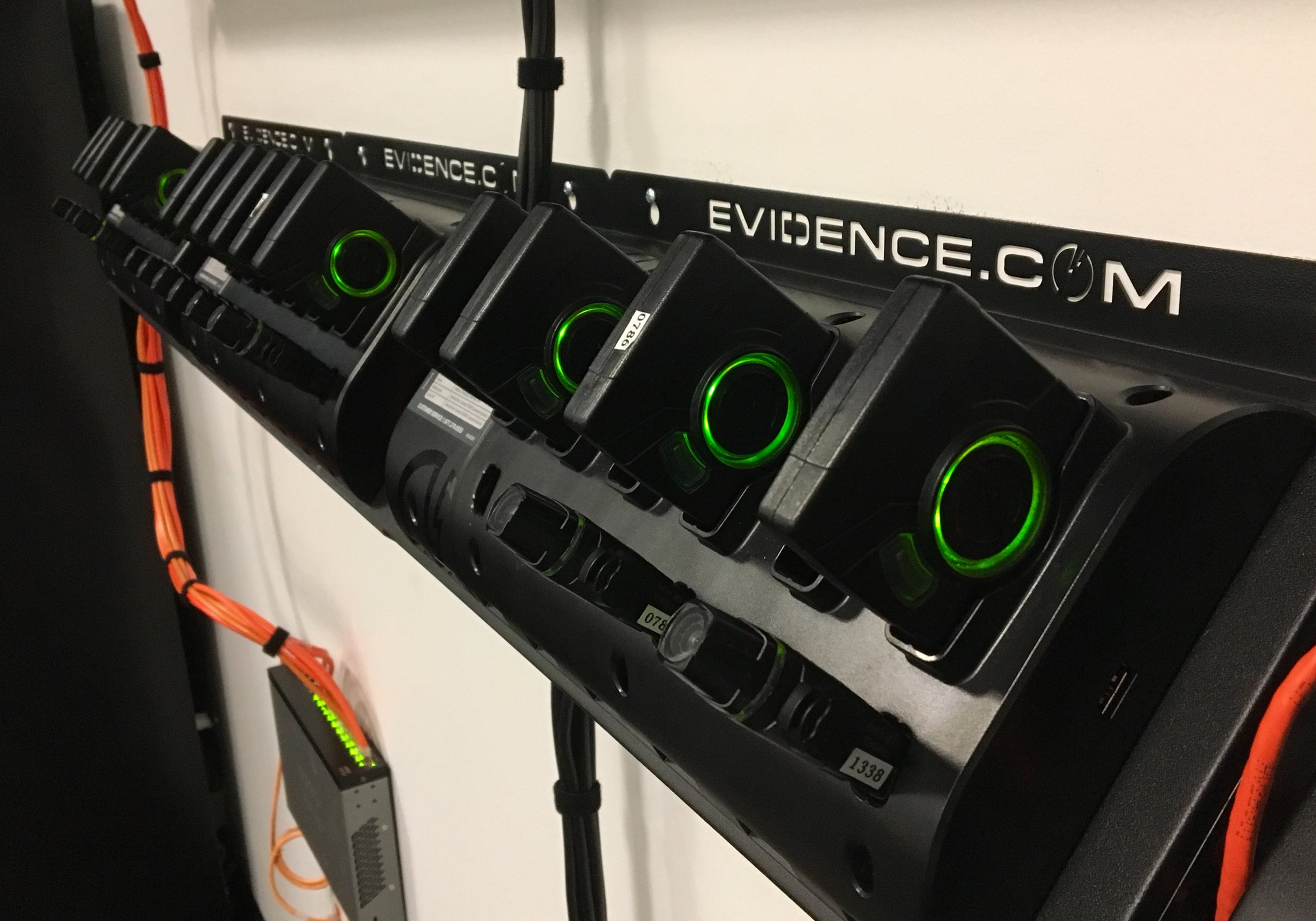 """The """"lipstick"""" style Axon Flex camera, with battery packs above, in their docking stations. The station both charges the pack and uploads any video stored. (Photo courtesy of Cape Coral Police Department)"""