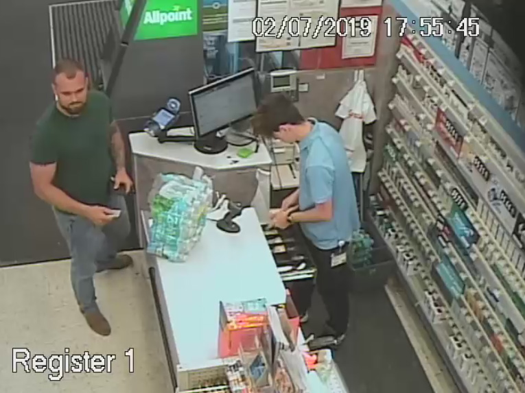 Suspect is on the left in the green shirt and blue jeans.