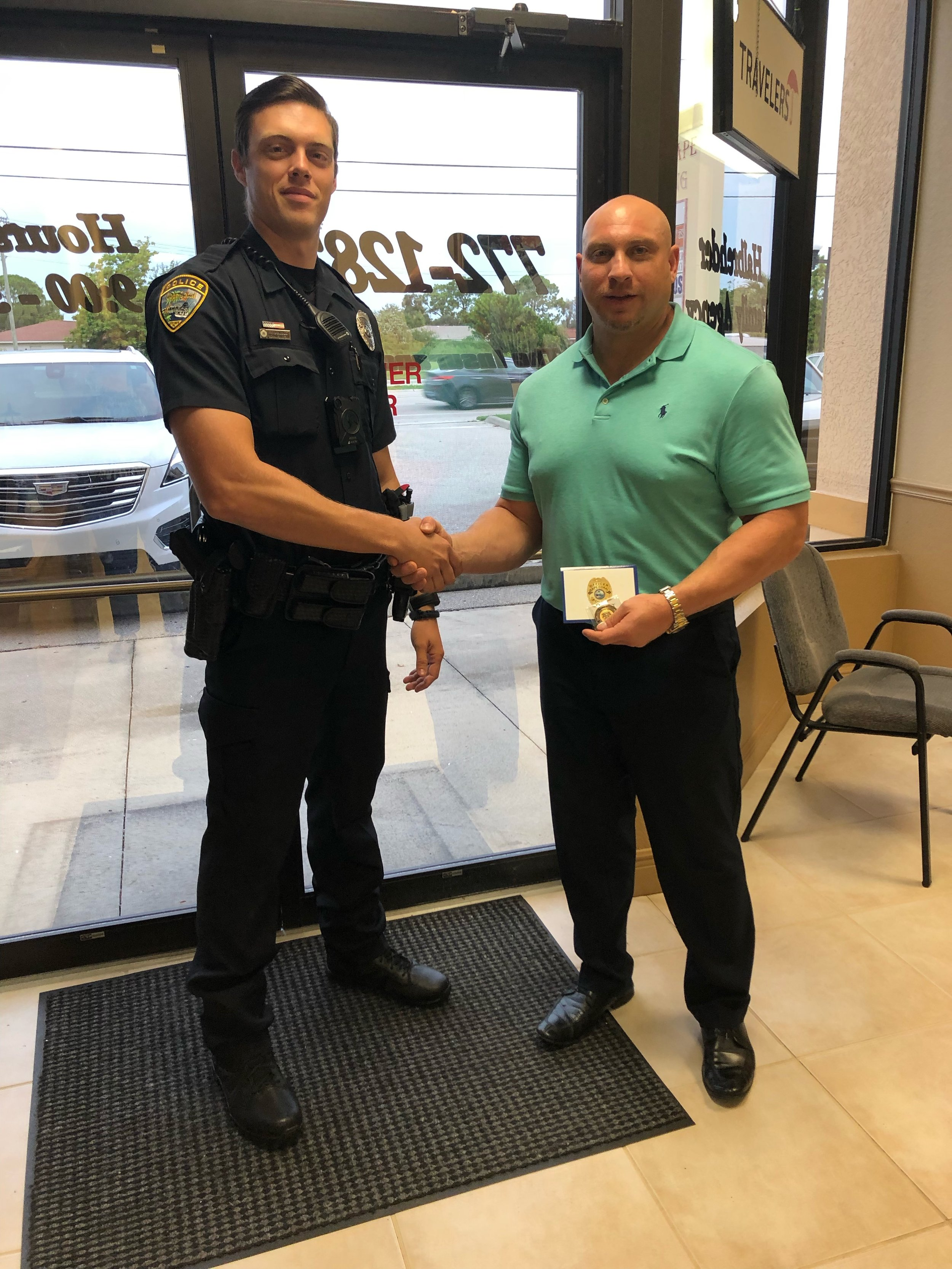 "CCPD Officer Patrick Dowdle presents Mr. Jay Halbrehder with the ""Citizen Commendable Action Coin"" for his lifesaving efforts."