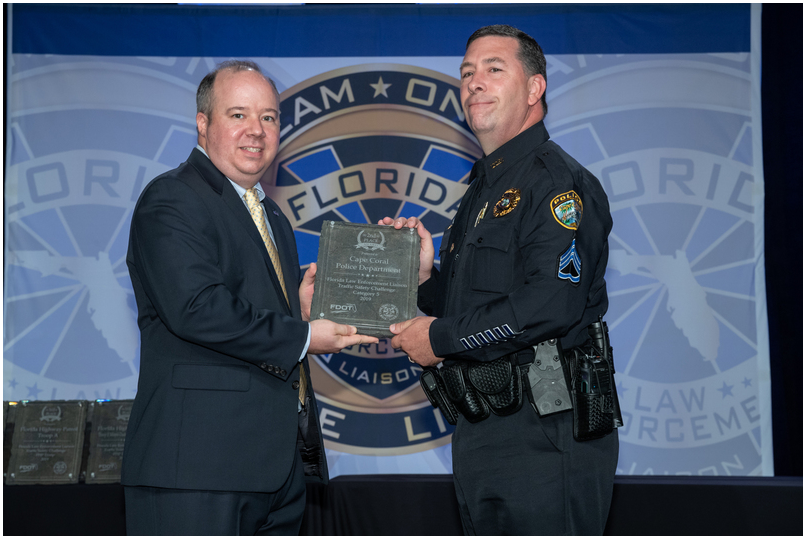 Sergeant James Lear accepts the plaque on behalf of the Cape Coral Police Department.