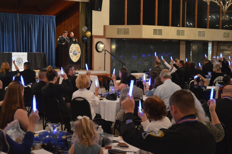 """Attendees hold blue glow sticks to remember those lost in the last year, as Chief Newlan recites """"A Police Officer's Prayer."""""""
