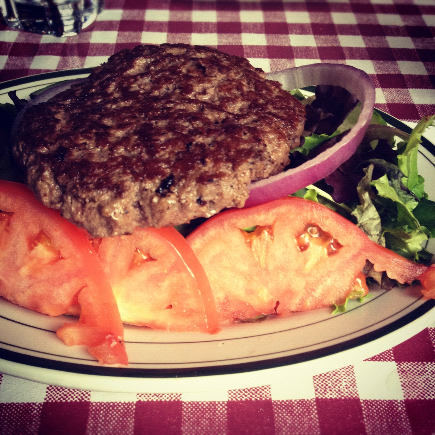 Pictured here is a griddled beef patty on top of a green salad from Bill's Burger—no dressing