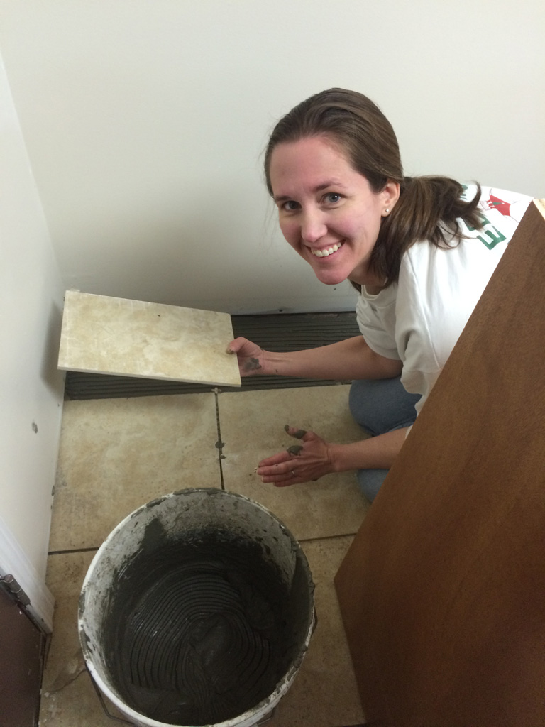 "Jennifer setting tile.  She thought it was good to ""practice"" on the area beneath the base cabinets first."
