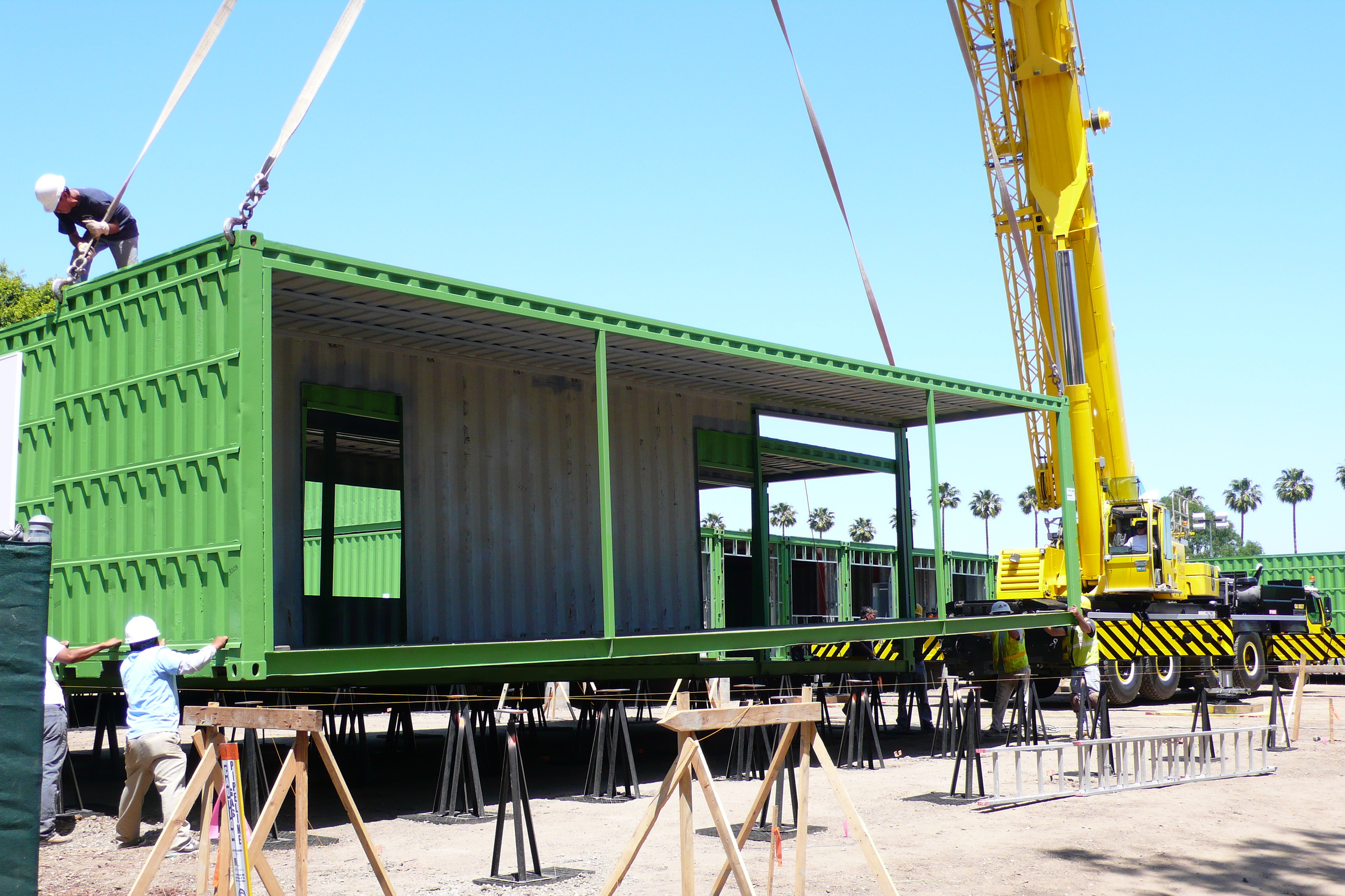 Modified steel shipping container being lowered to school site.