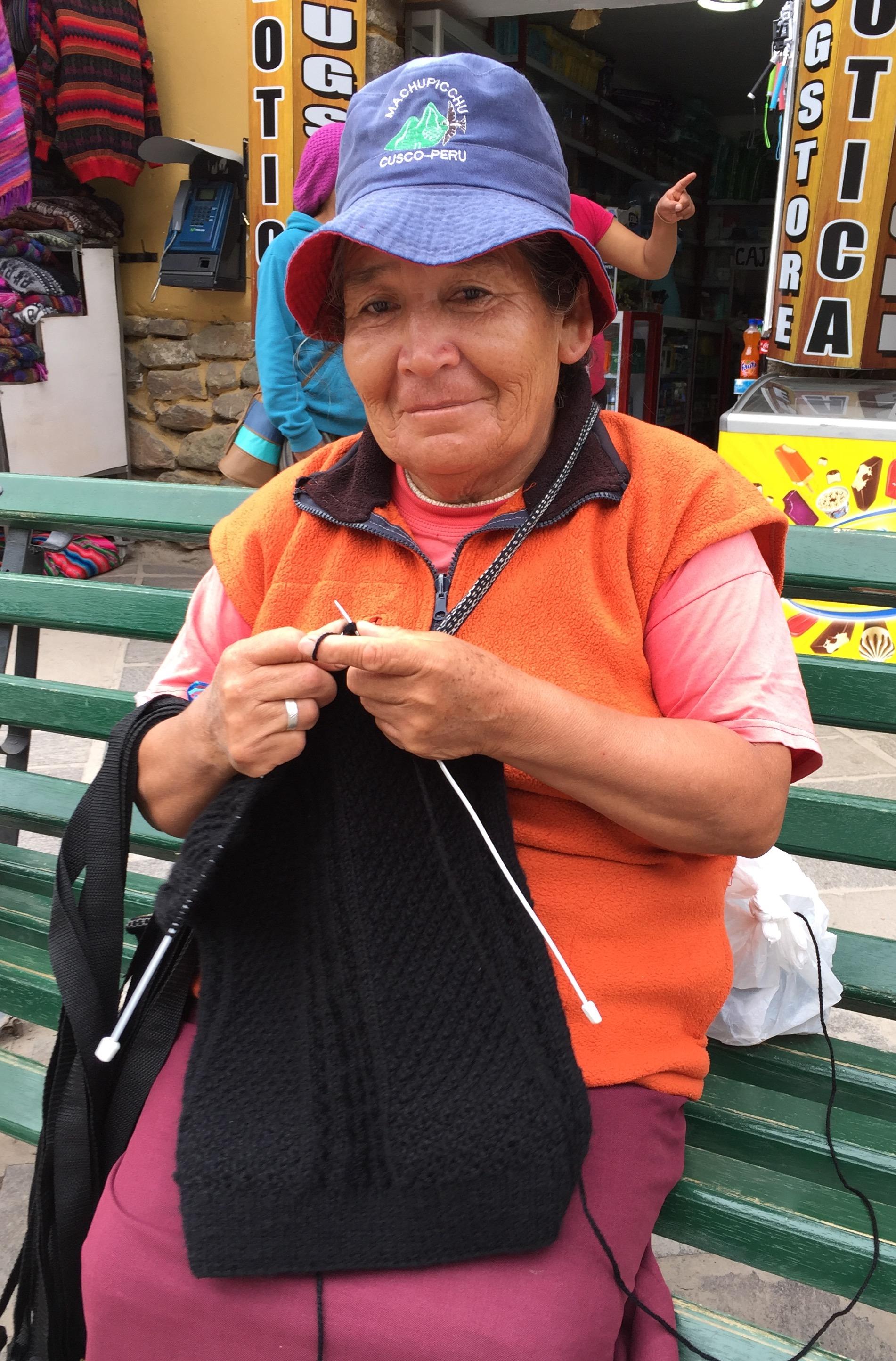 Kvinne som strikker på tradisjonelt vis. Her er mønsteret perlestrikk og fletter.