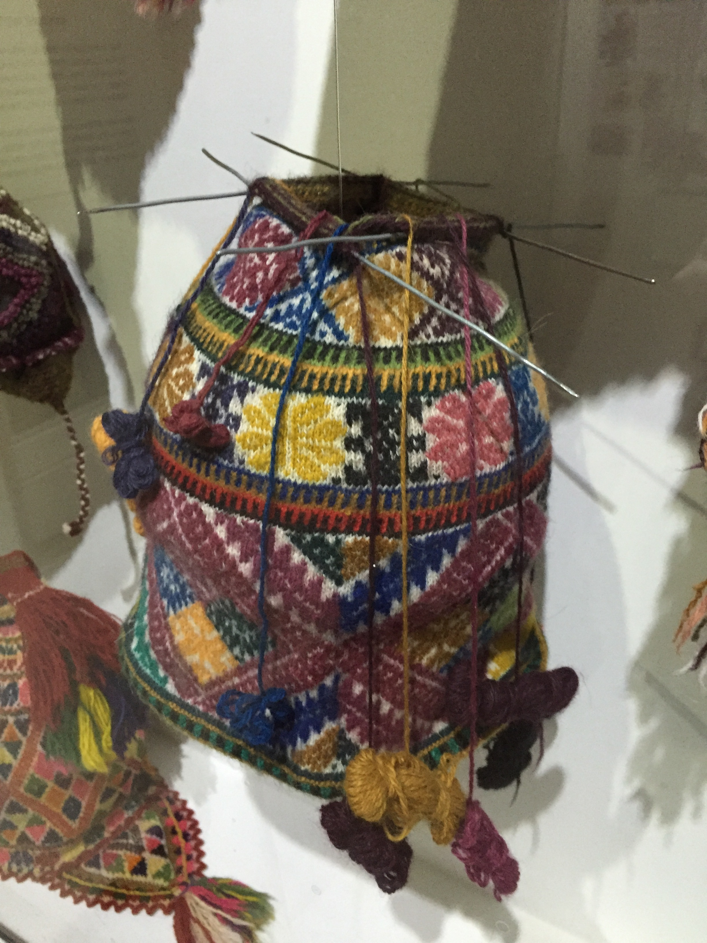 Også på museet finnes en lue som ennå ikke er helt ferdig, og hvor strikkepinnene sitter i. De er relativt bulkete. Her kan man se hvordan det strikkes med mange små garnnøster i ulike farger.