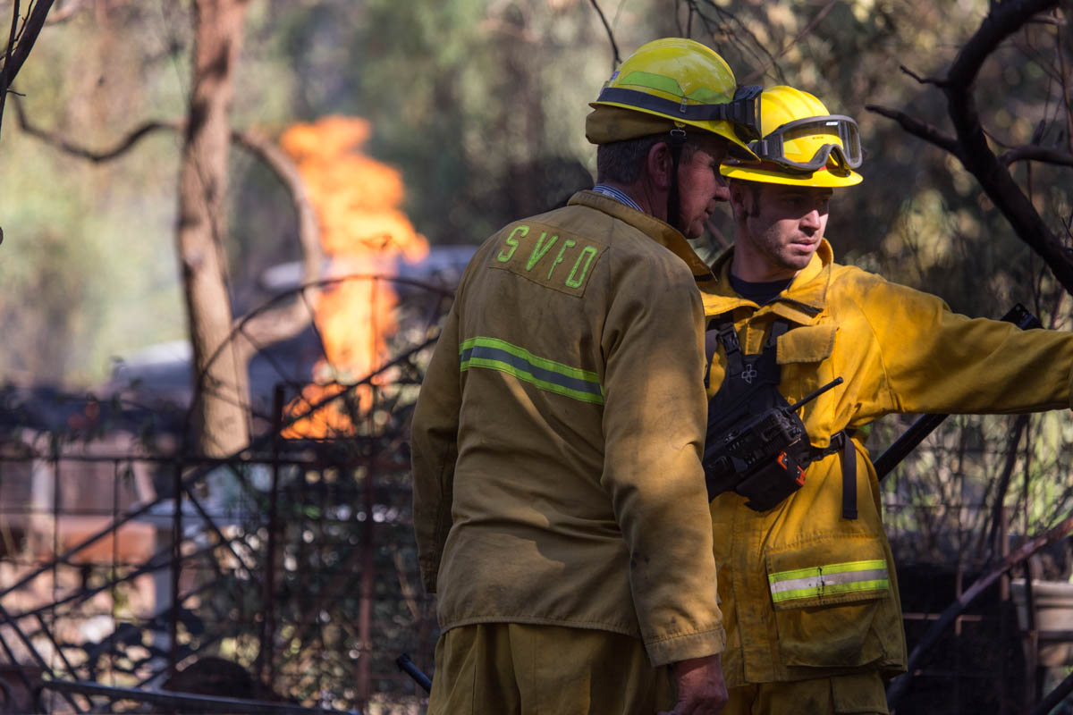 Sonoma, CA 10/14/17:An open gas line burns in the background as firefighters put out spot fires on a property burned by the Partrick fire on Castle Rd. in the city of Sonoma.