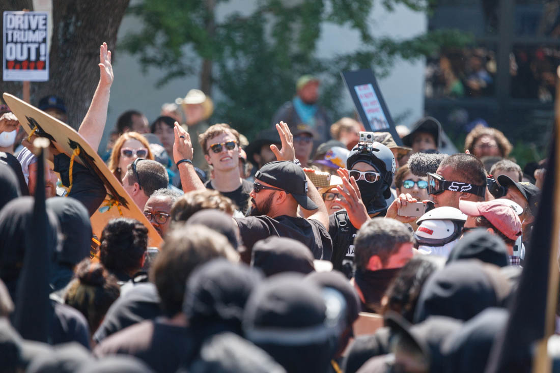 Joey Gibson is surrounded by black clad 'Antifa' in Berkeley during an 'anti-Marxist' rally. Shortly after, Gibson was detained by police for his own safety. Gibson had attempted to organize a 'Patriot Prayer' rally in San Francisco the previous morning, but had to cancel due to large scale protests. 8/27/17
