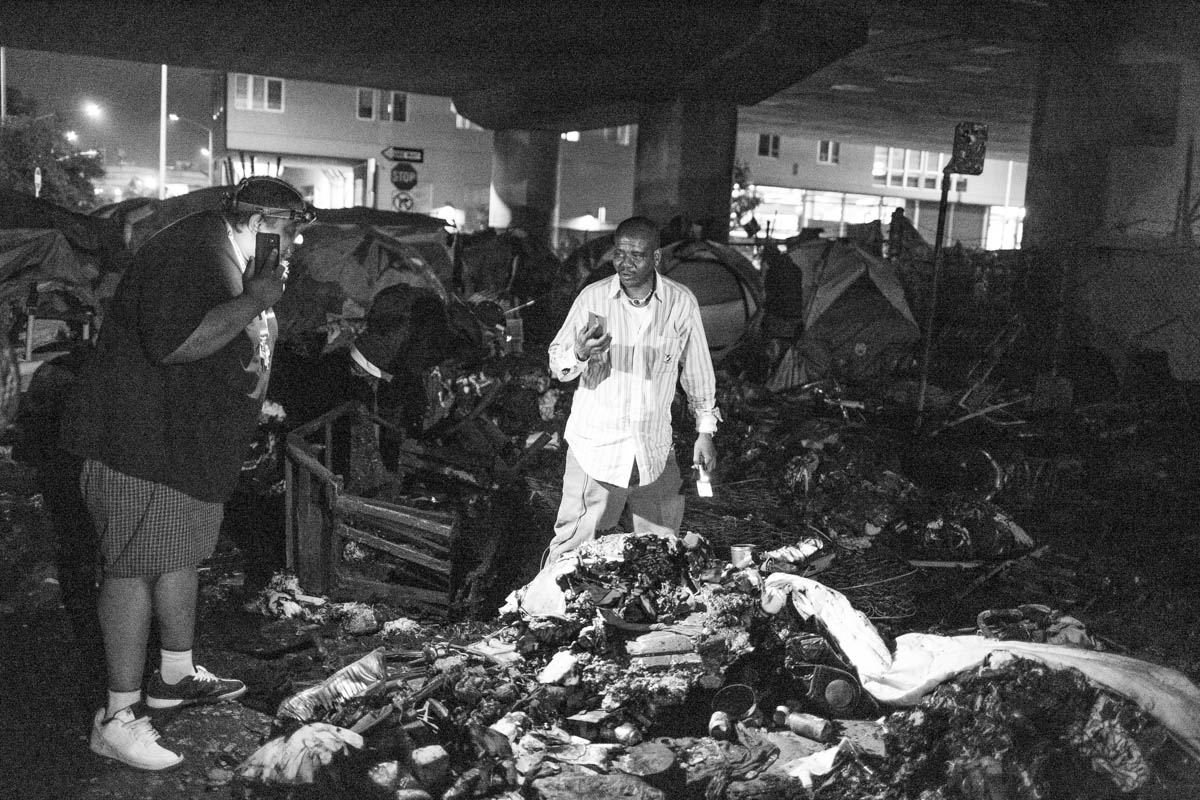 A man searches through the charred remains of tents after a large fire at an encampment on Peralta St. Oakland, CA