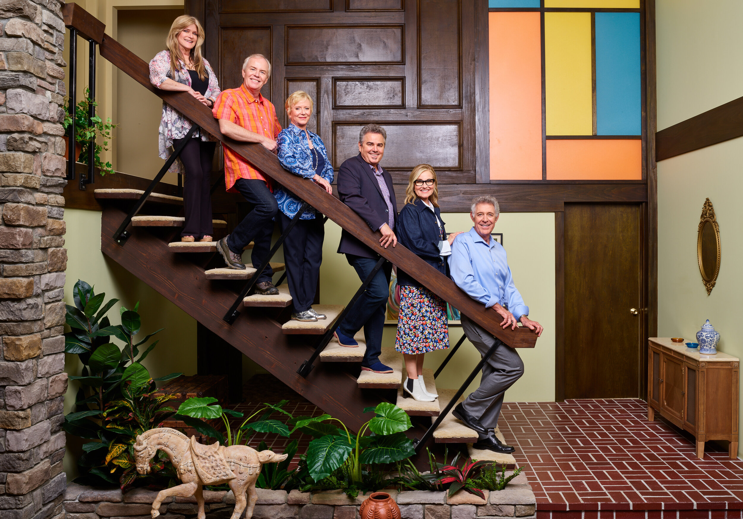 The original Brady Bunch cast (left to right: Susan Olsen, Mike Lookinland, Eve Plumb, Christopher Knight, Maureen McCormick, and Barry Williams) recreate the iconic Brady family portrait at the recently renovated Brady home in Studio City, California, as seen on A Very Brady Renovation.