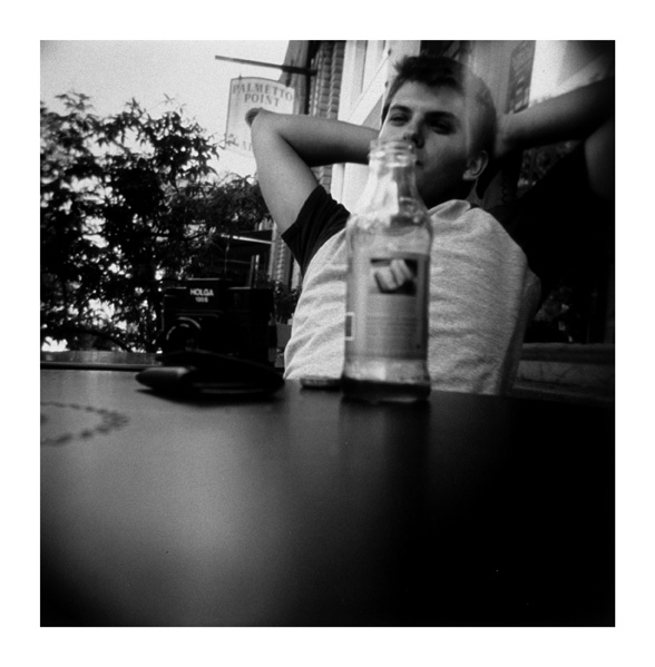 My good friend Daniel, photographed with a Holga resting on the table. I took this shot while we took a break from walking during a shooting expedition around Savannah with our Holgas (you can see his resting on the table in front of him).