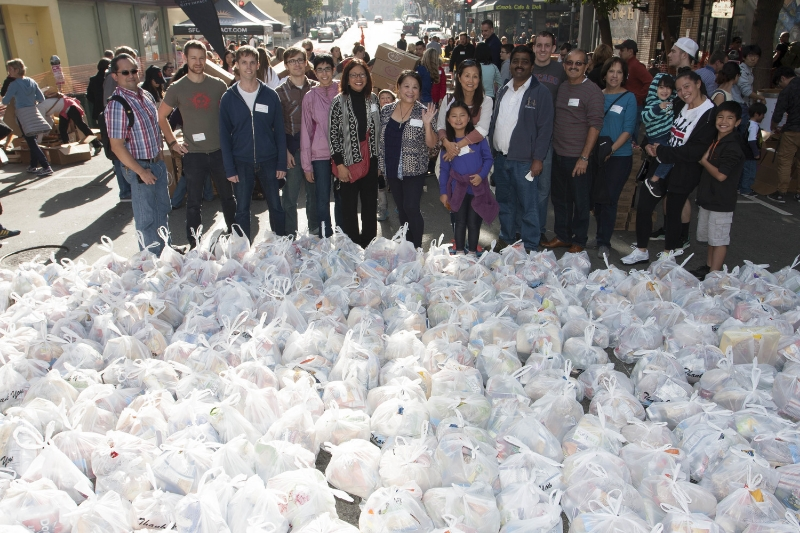 Volunteers standing with prepared groceries for Tenderloin residents