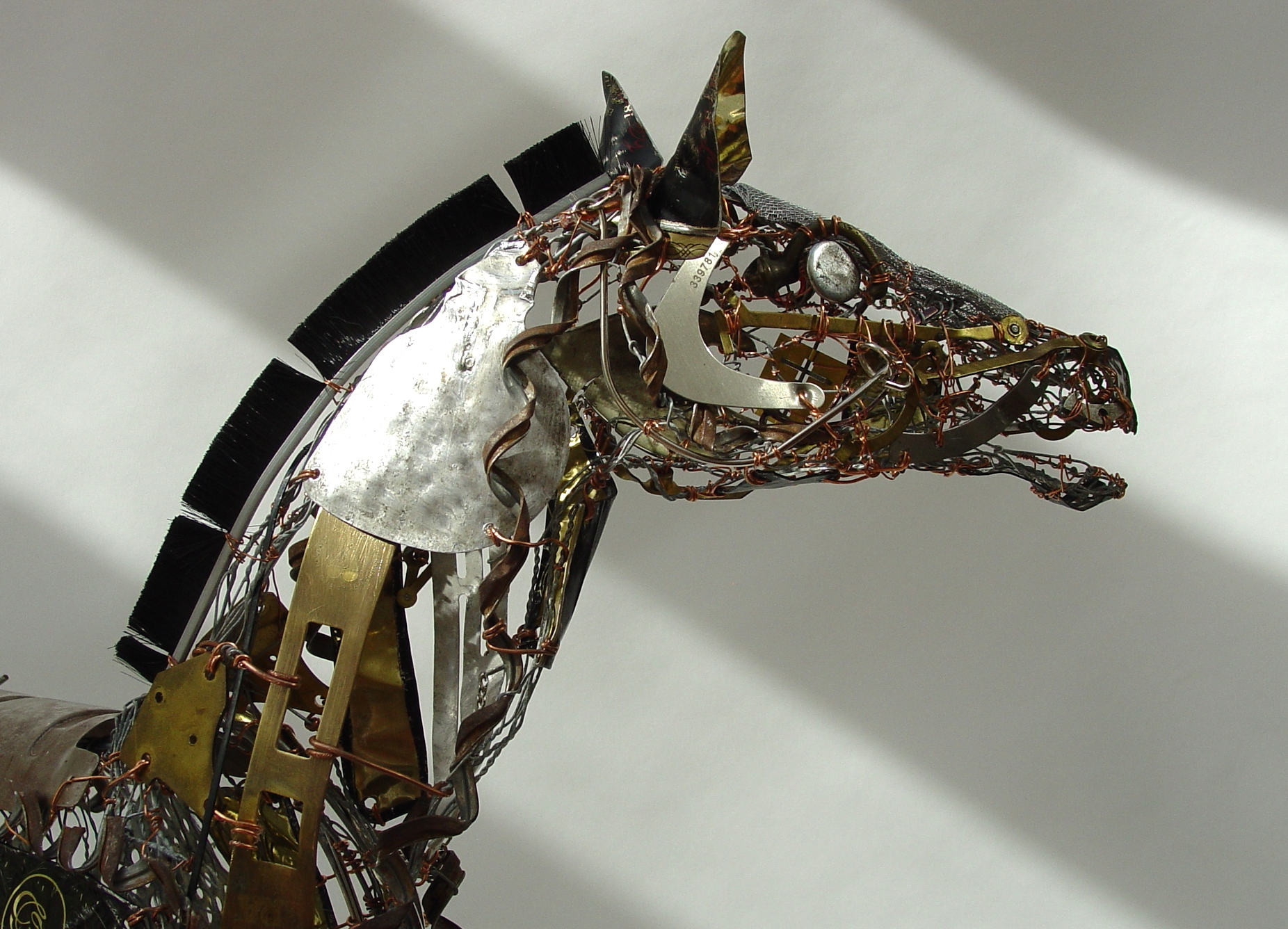 This lively piece is made with a wire armature onto which I have attached a variety of found, recycled and now 'upcycled' materials. Close inspection will reveal dog leads, hinges, old clock parts,keys and cutlery amongst many other items. I love this piece and hope it will find fans in Scotland.