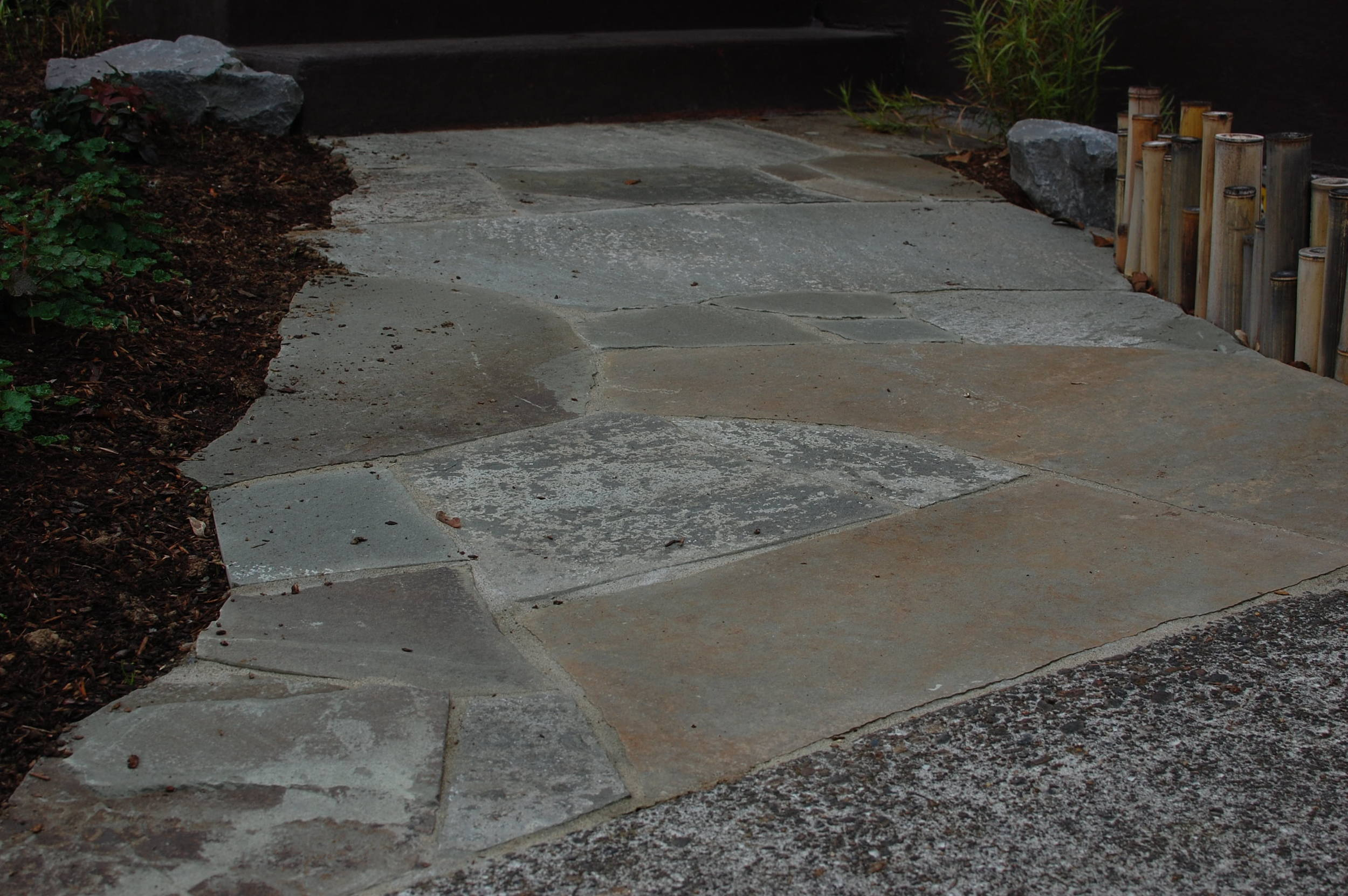 Rustic bluestone path set in sand.