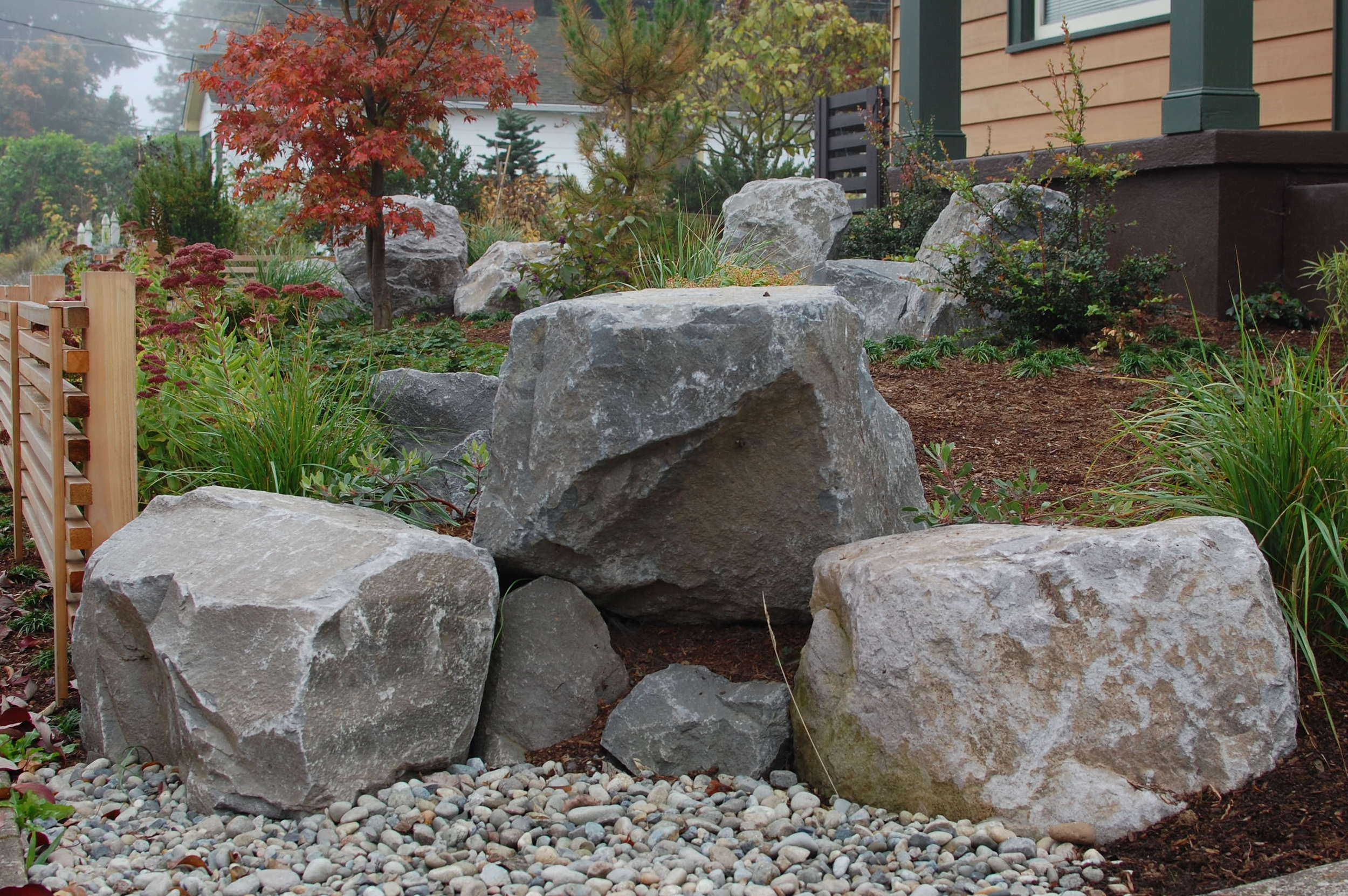 Boulder grouping by the main entrance, with a pea gravel pond.