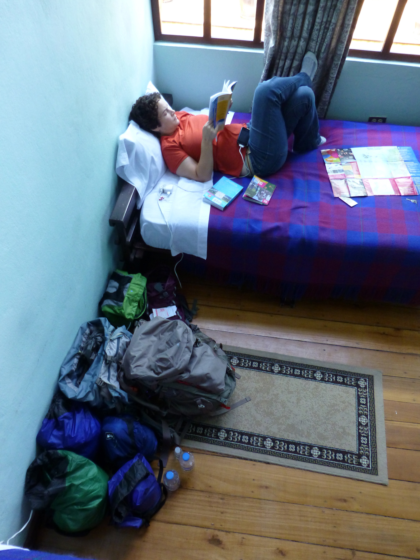 Katie relaxing in our Quito hostel alongside our worldly possessions. A controlled explosion at the moment.